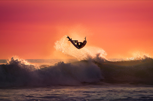 Surfer jumping on top of a Wave