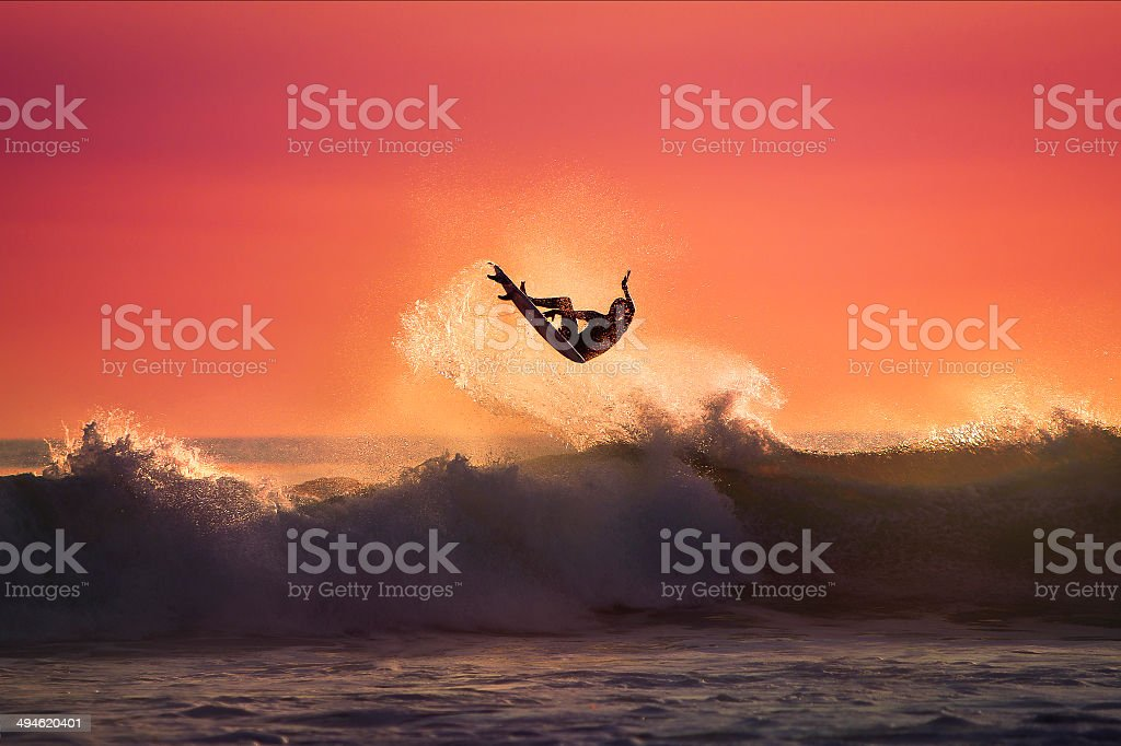 Surfer jumping on top of a Wave stock photo