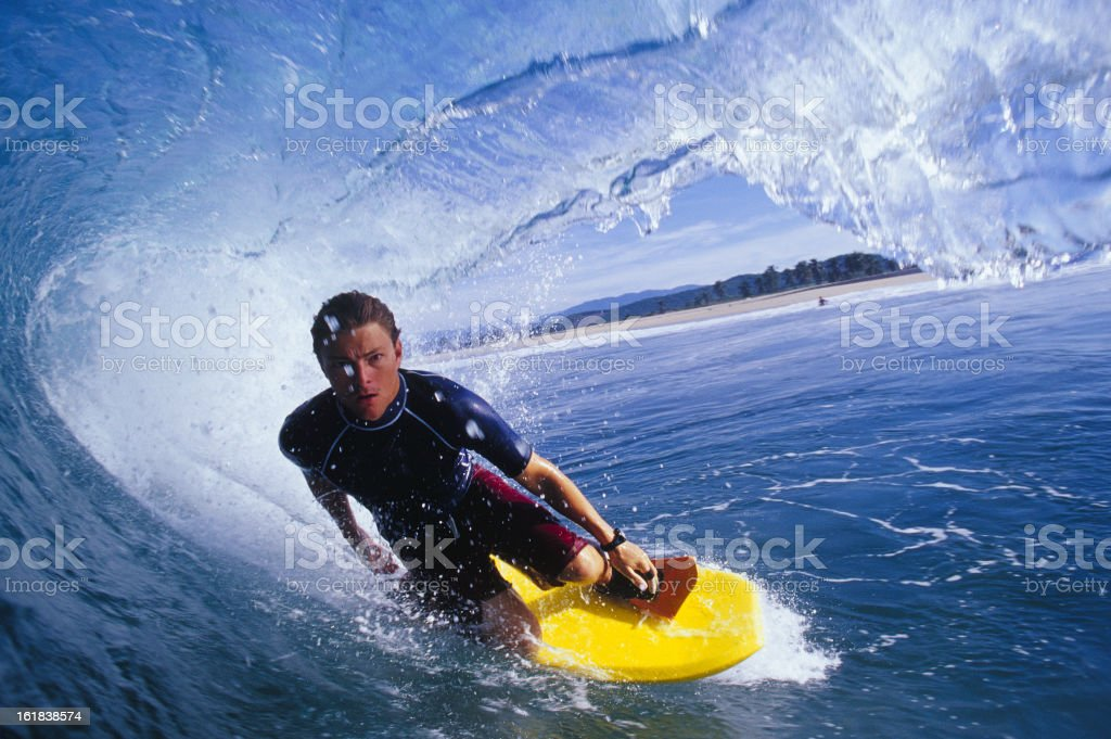 A surfer, kneeling on his yellow board, inside a wave stock photo