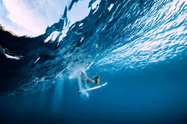 Surfer machen Ente tauchen unter Wasser. Surfgirl tauchen unter großer Welle – Foto