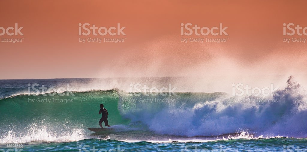 Surfer on Blue Ocean Wave in Bali stock photo