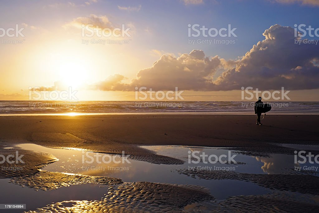 Surfer  on the beach at sunset royalty-free stock photo
