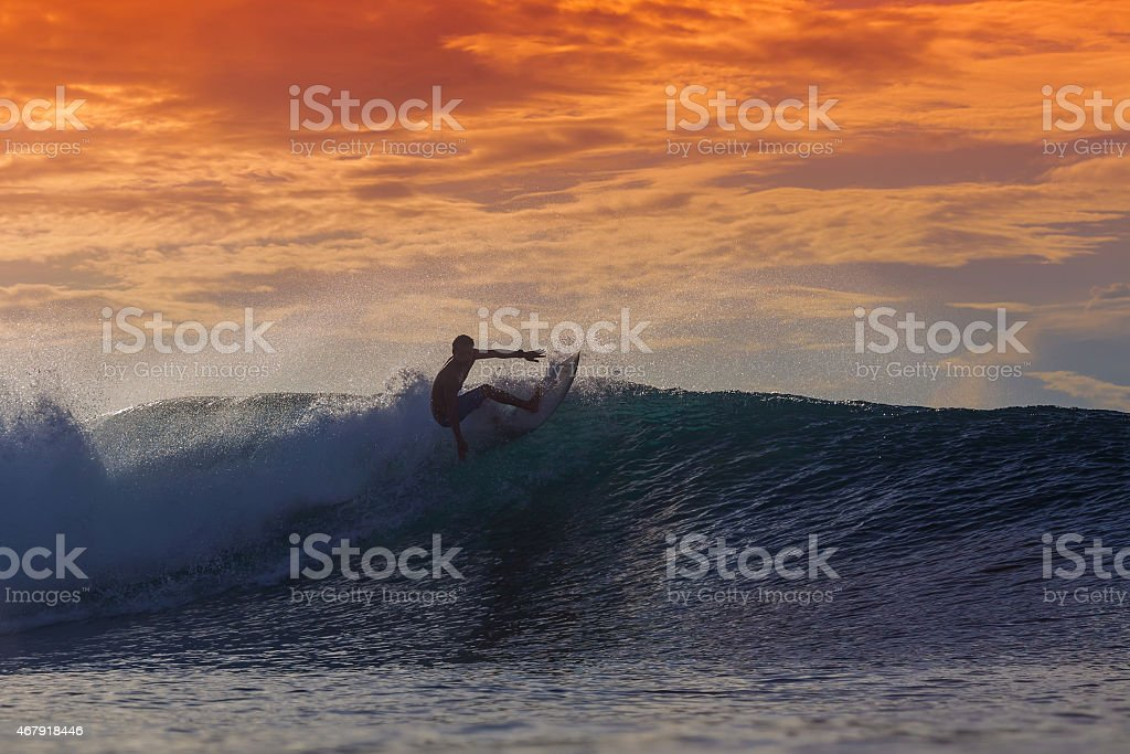 Surfer on the waves at sunset  stock photo