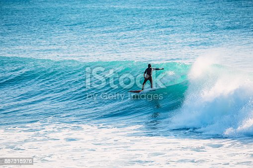 istock Surfer ride on blue wave. Winter surfing in ocean 887318976