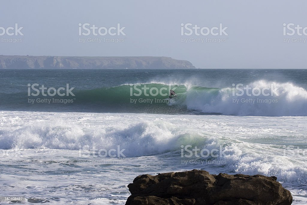 Surfer rides a wave at a reef in Porthleven stock photo