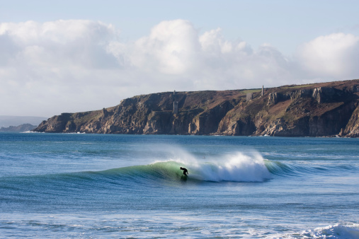 Surfer rides a wave at a reef in Porthleven