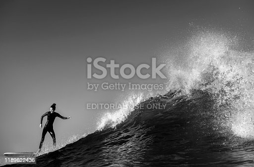 Sydney, Australia - July 06 2018: Black and white photo of a woman riding a large wave at Bronte Beach, Sydney Australia