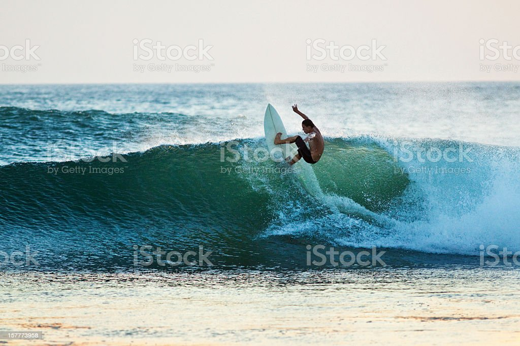 Surfer riding a wave off the top stock photo