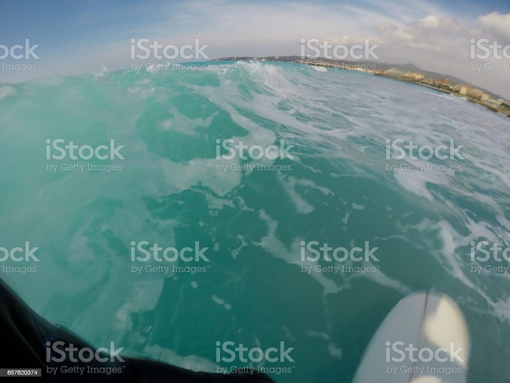 Surfer riding a wave on turquoise sea, point of view