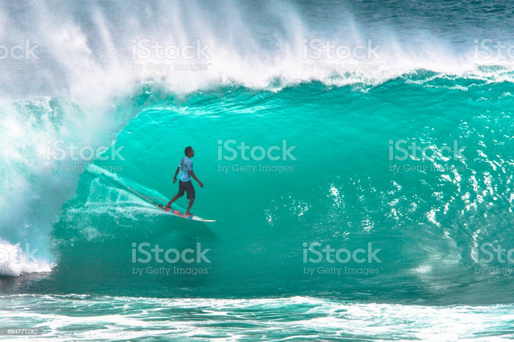 Surfer riding big green wave in Bali stock photo