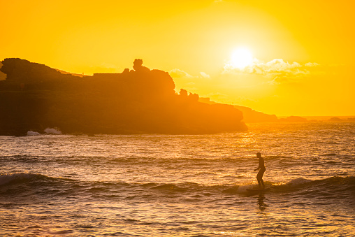 Surfer riding waves at golden sunset beach St Ives Cornwall