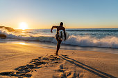 Surfer running into the water carrying his board with a beautiful sunrise at the background - sports concepts