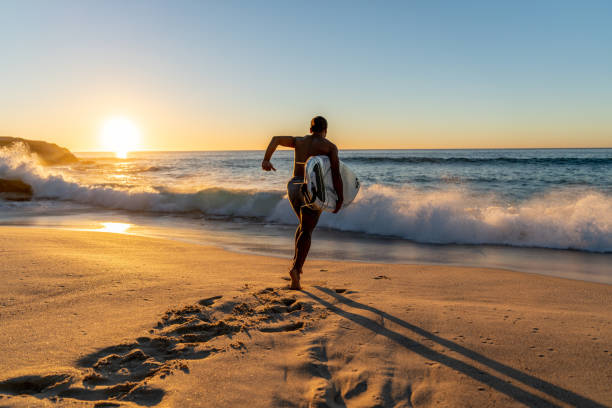 surfer running into the water carrying his board - surf foto e immagini stock