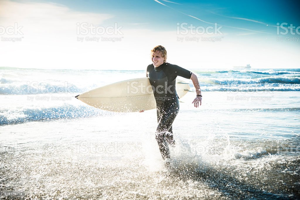 surfer running on the beach stock photo