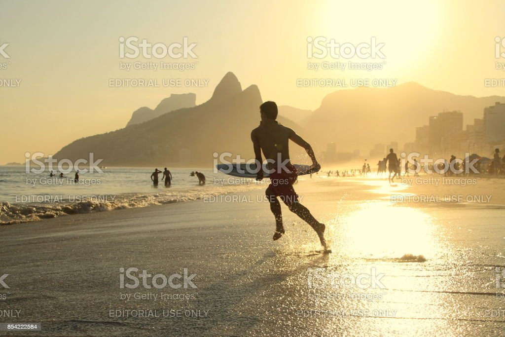 Surfer running to the sea stock photo