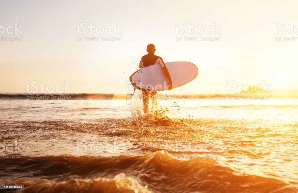 dcb42fefc9 Surfer runs with surfboard towards ocean waves ta sunset time royalty-free  stock photo