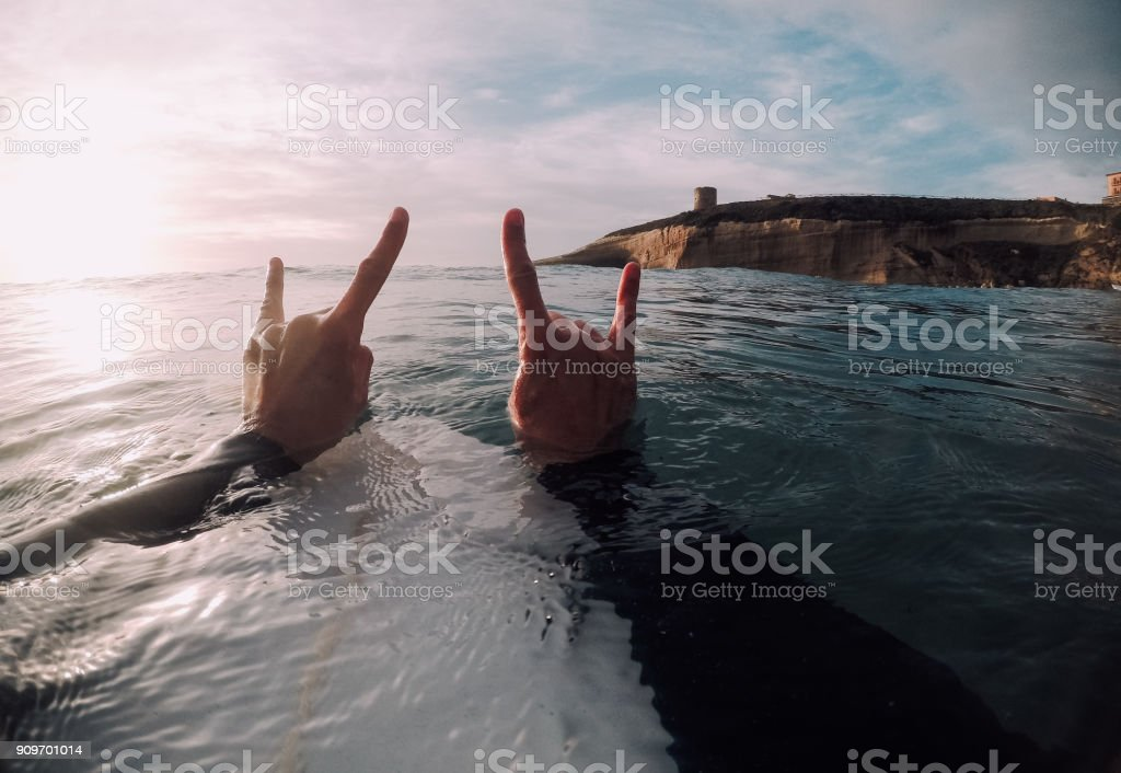 Surfer showing horn sign with both hands in the sea (POV) stock photo