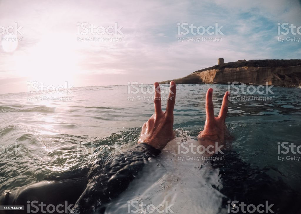Surfer showing peace sign with both hands in the sea (POV) stock photo