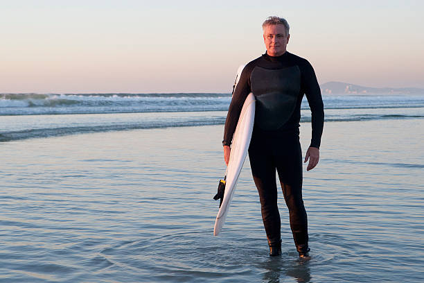 Surfer standing in water  wetsuit stock pictures, royalty-free photos & images