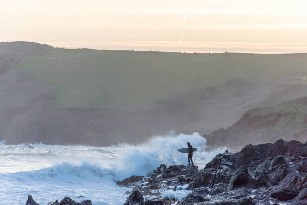 Surfer standing on rocky shore attempting evening surf in rough sea. stock photo