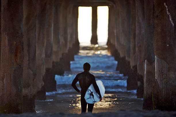 Surfer Standing Under the Pier stock photo