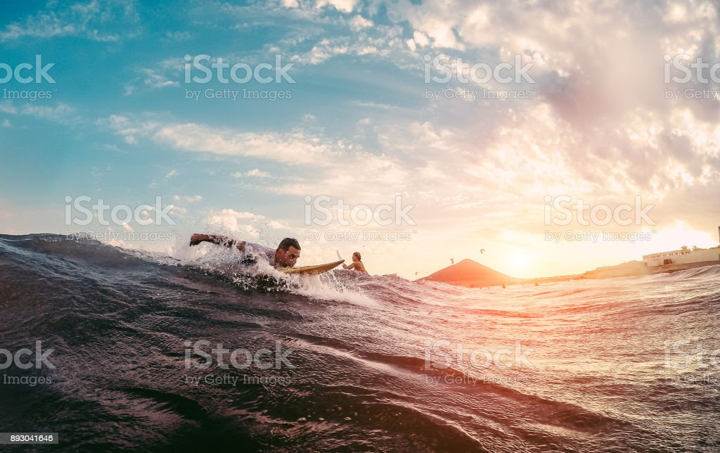 Surfer starting to ride a wave at sunset - Man surfin outdoor inside ocean- Extreme sport and vacation concept - Focus on male body stock photo