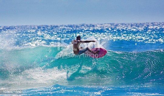 A local Hawaiian surfer surfing at Poipu Beach, Kauai, Hawaii.