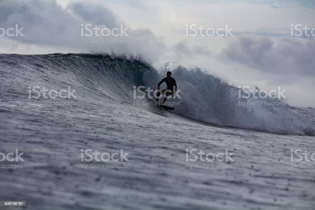 Surfer Surfing In Rain With Raindrops Falling On Ocean
