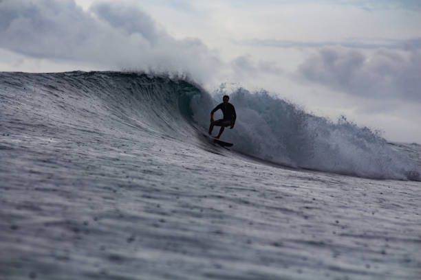 Surfer surfing in rain with raindrops falling on ocean surface stock photo