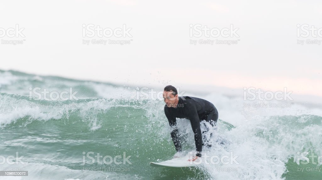 Surfer taking off on a wave stock photo