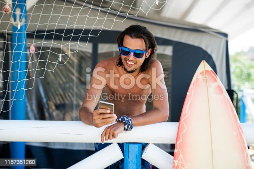 Young man surfer relaxing and using smart phone, surfer leaning on porch and using smart phone.