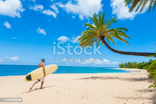Surfer walking on the beach with his surfboard.