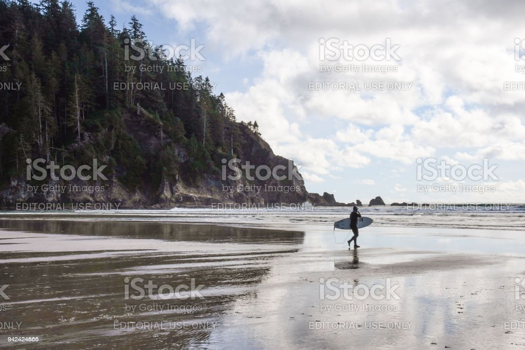Surfer walking to ocean stock photo