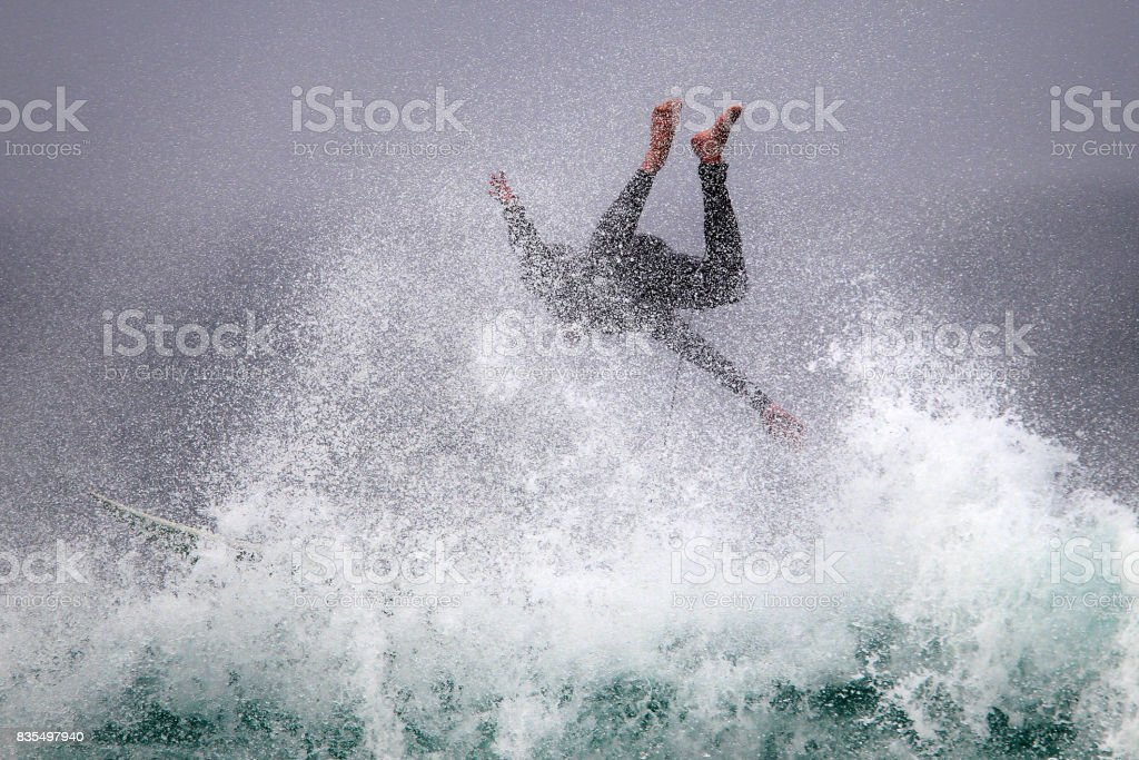 A surfer wipes out on a big wave. stock photo