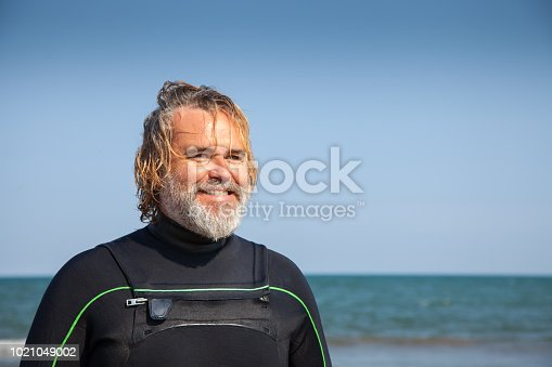 Surfer with a carefree attitude after leaving the sea in the mediterranean coast