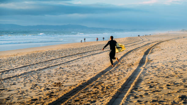 Surfer with board running towards the water at Portugal's beautiful Caparica beach stock photo
