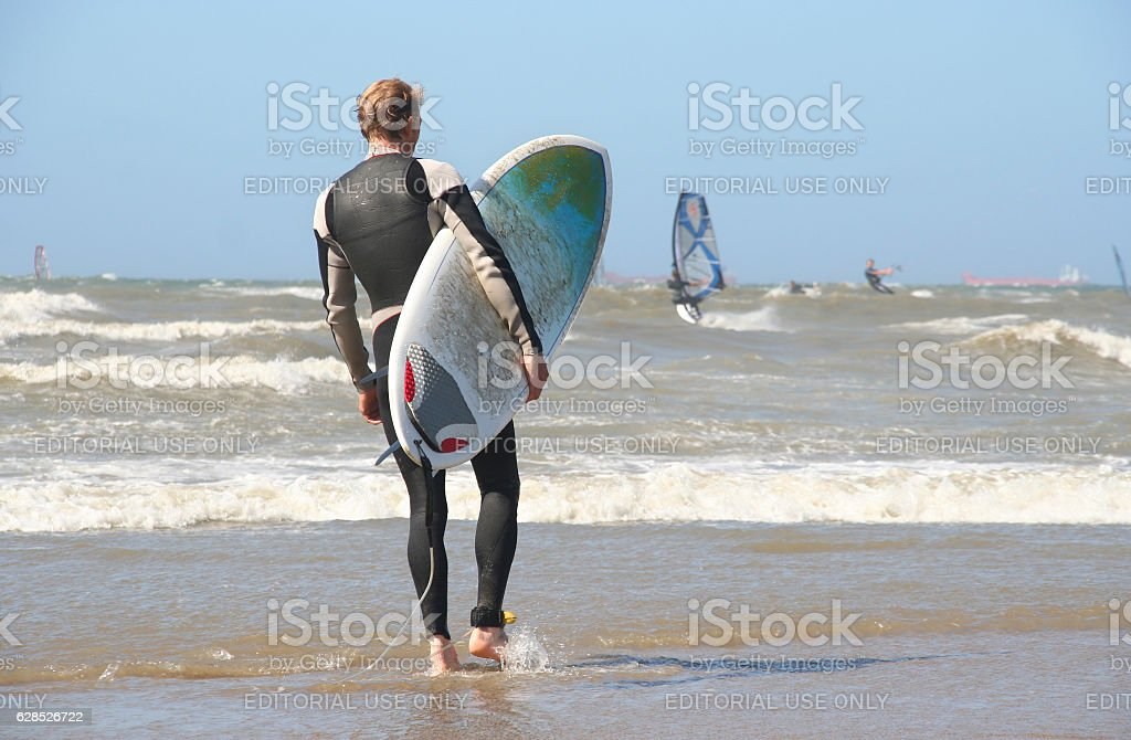 Surfer with surf board on the beach stock photo