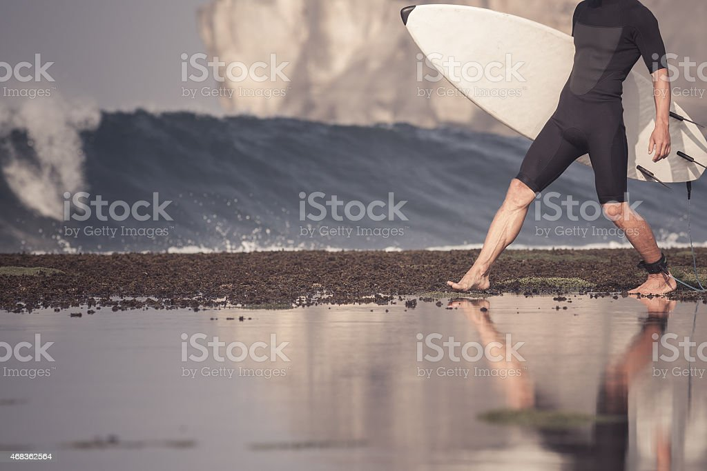Surfer with surfboard on a coastline royalty-free stock photo