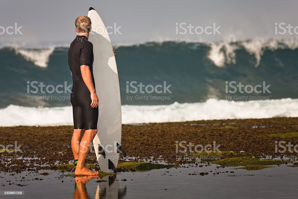 Surfer with surfboard on a coastline stock photo