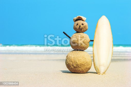 joyful Sandman surfer with surfboard on sand against turquoise sea water. Christmas and new year concept on a tropical beach. Bright colors. concept of surf.