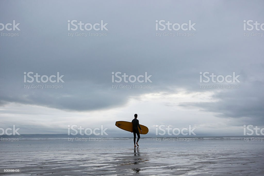 Surfer With Surfboard Walking Towards Sea On Beach royalty-free stock photo