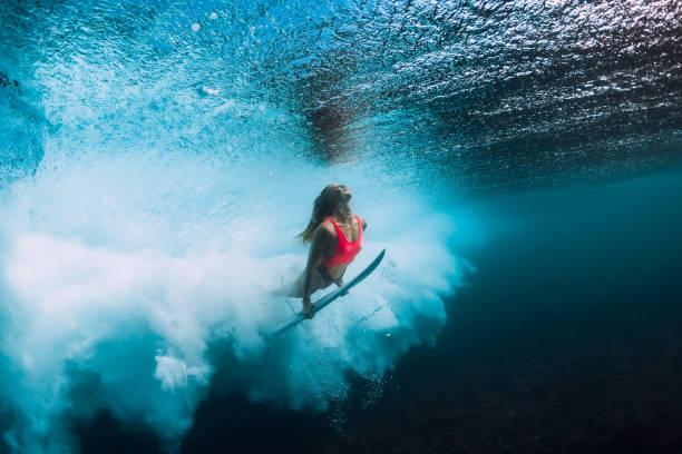 mujer de surfista con buceo tabla de surf bajo el agua con bajo la ola del océano. - surf fotografías e imágenes de stock
