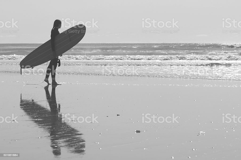 Surfergirl with longboard on the beach stock photo