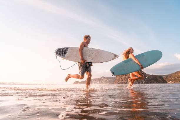 Surfers at beach. stock photo
