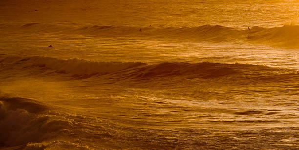 surfers at fistral beach, newquay during winter sunset - cornwall stock pictures, royalty-free photos & images