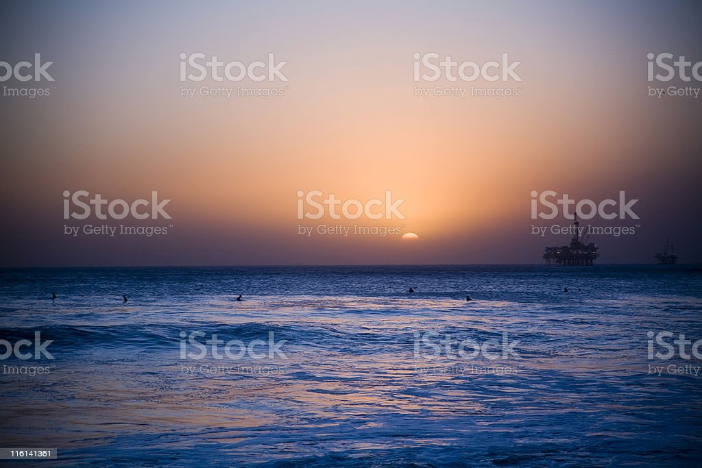 surfers at sunset stock photo