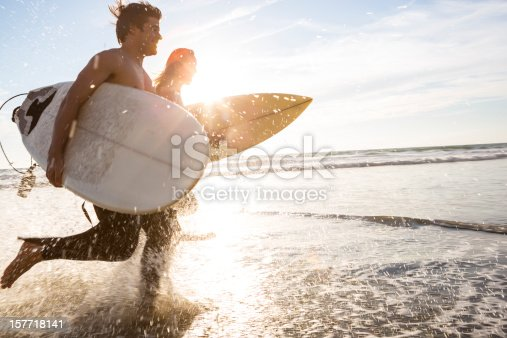 Two surfers run through the surf at sunset