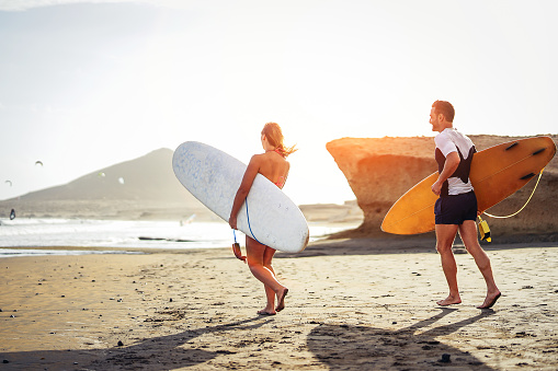 istock Surfers couple running together with surfboards on the beach at sunset - Sporty friends having fun going to surf - Travel, vacation, sport lifestyle concept 1082886730