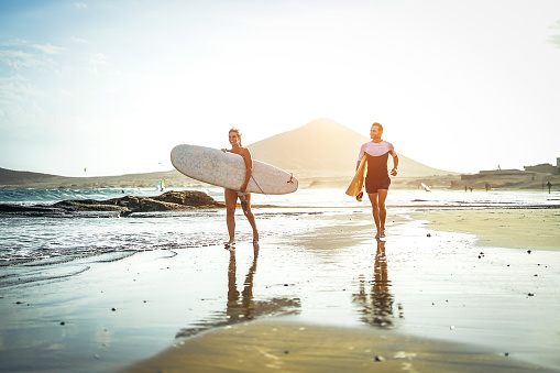 istock Surfers couple running together with surfboards on the beach at sunset - Sports friends having fun surfing - Travel, holidays, sport lifestyle concept 937777360