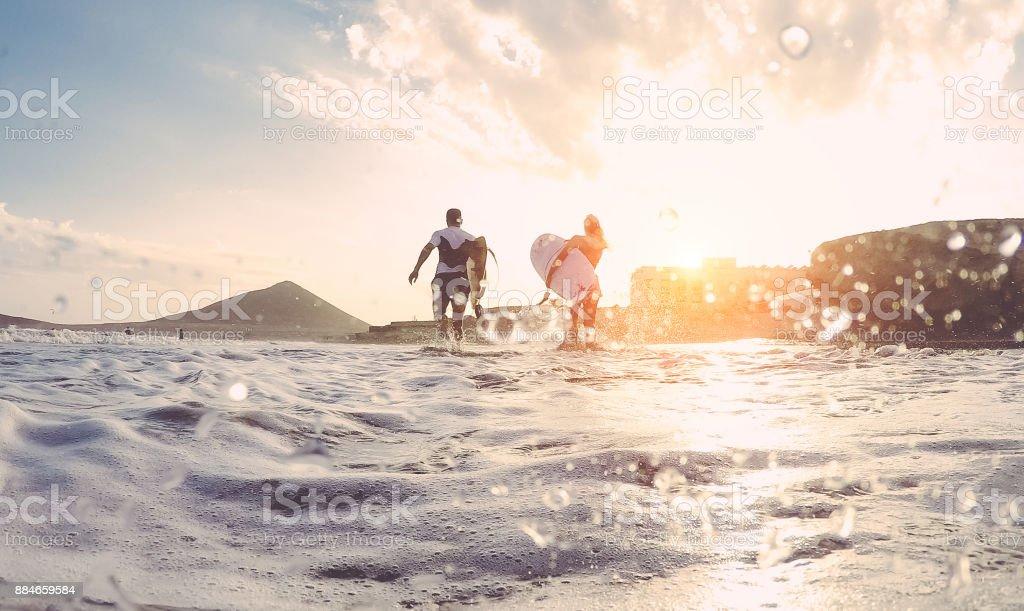 Surfer-paar läuft mit Surfbrettern auf dem Strand - sportliche Leute, die Spaß an sonnigen Tagen - Extreme Sport, Reisen und Urlaub Konzept - Fokus auf Körper - Wasser vor der Kamera Objektiv – Foto